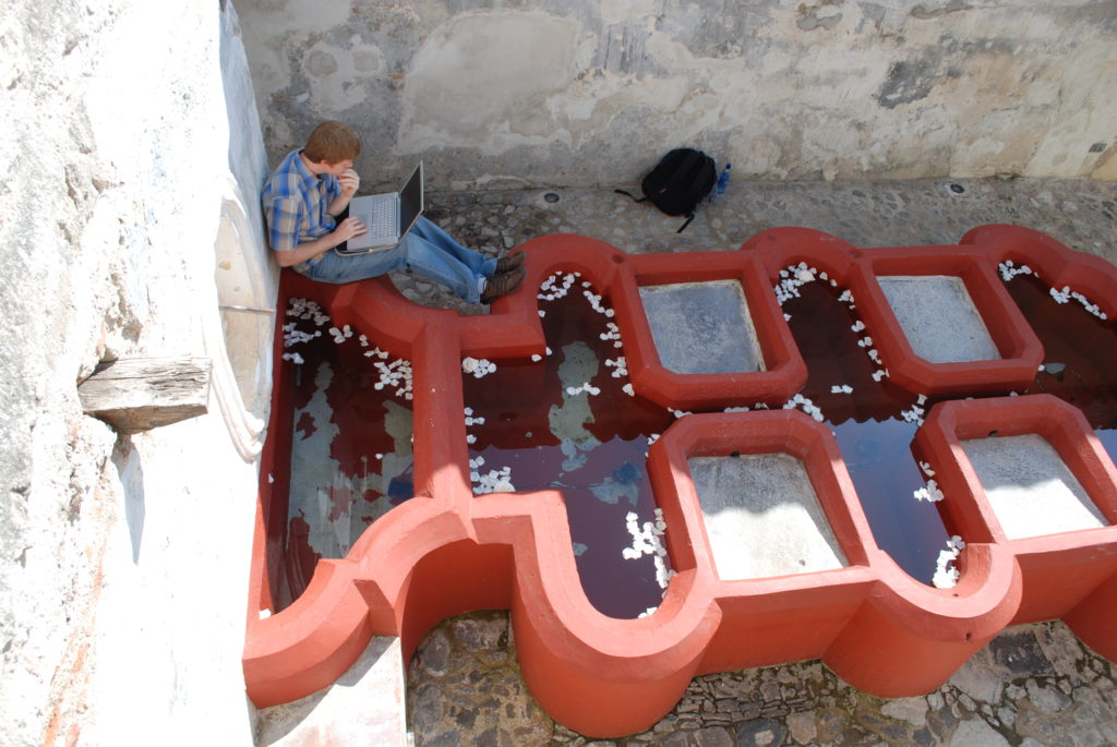 student looking at laptop while sitting on unique red painted fountain pool architecture in stone courtyard