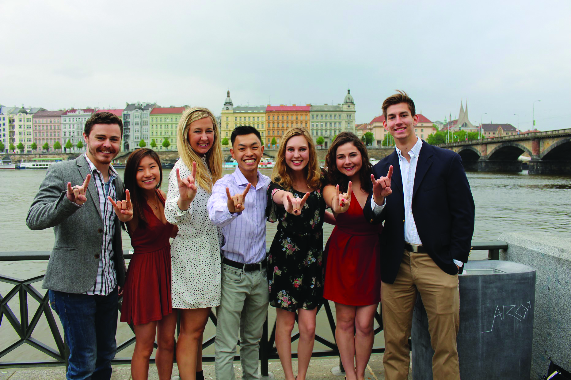 A diverse mix of UT abroad students pose with the Hook 'Em horns on a pier on a rivers edge with buildings in the background