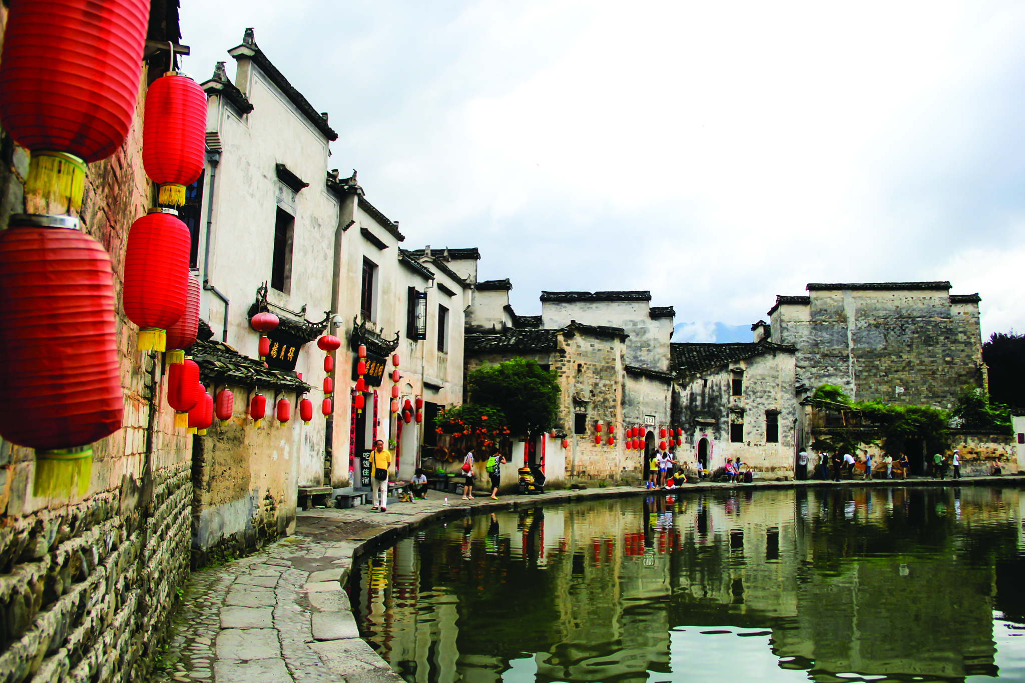 Canal in Hongcun, China with hanging red lanterns from buildings lining the canal.