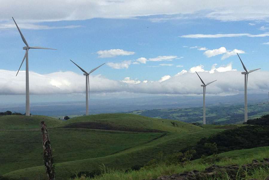 windmills in a green field with blue skies and clouds