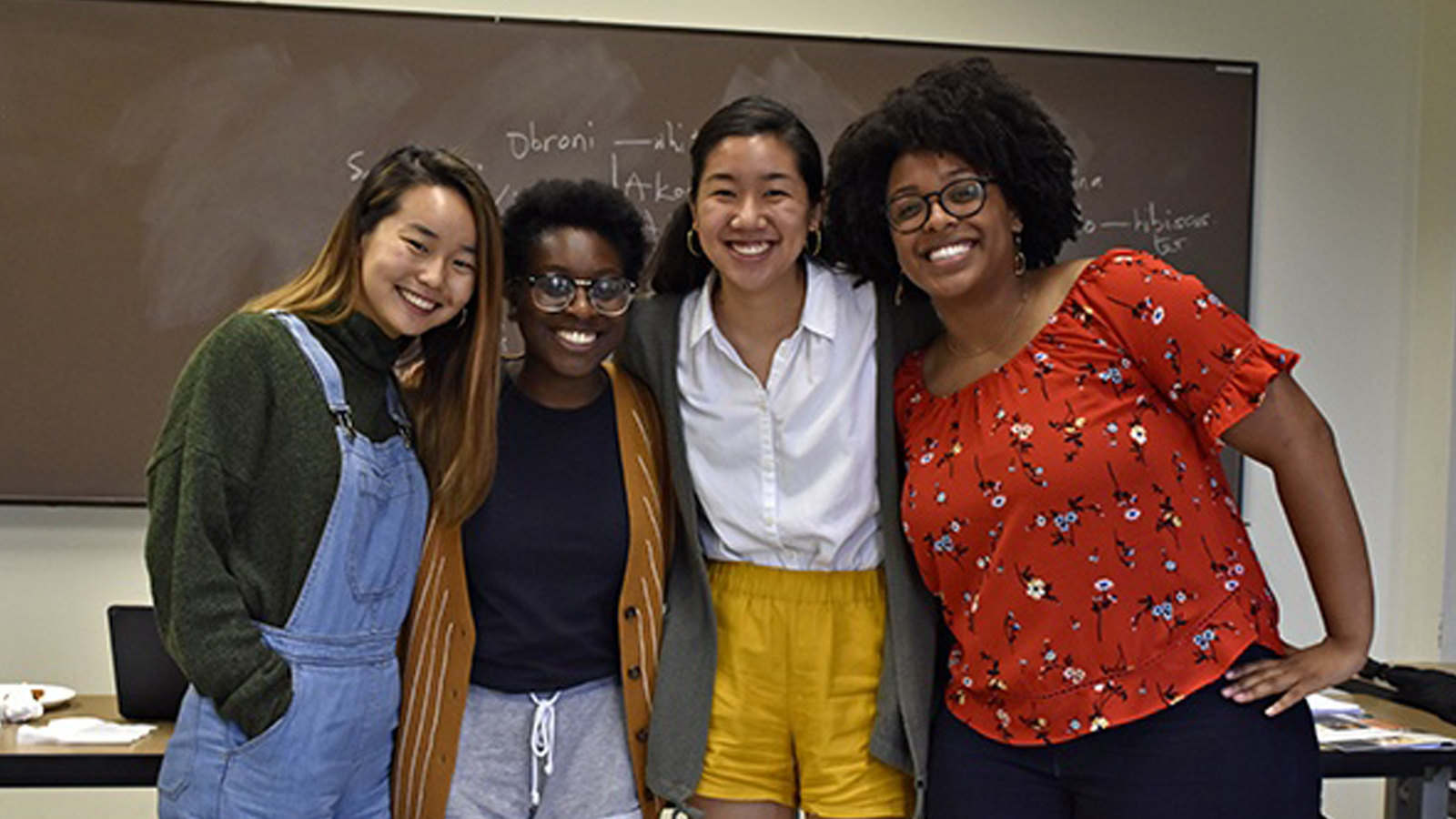 A team of students — Timia Bethea, Christina Cho, Vida Nwadiei and Rebecca Chen — stand together in front of classroom chalkboard, smiling.