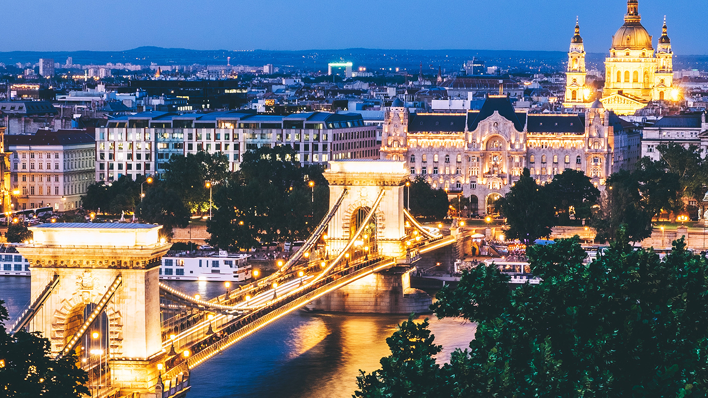 a view of budapest with a lit up bridge
